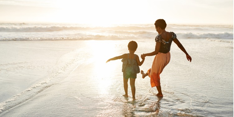 an image of a mother and daughter playing in the shallow sea water on the beach