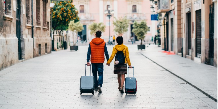 an image of a couple walking together on holiday wearing amber and red jackets