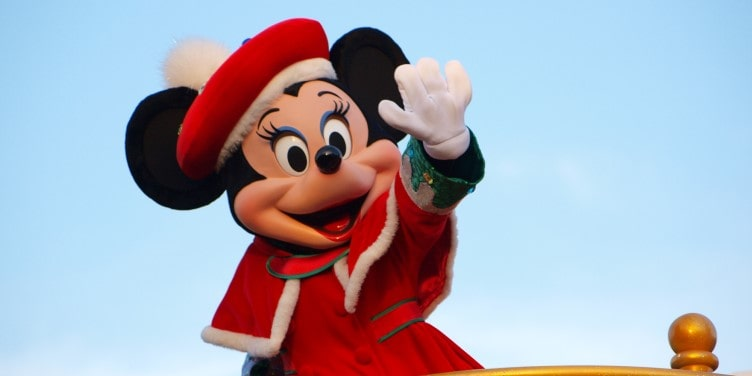 Minnie Mouse waving at crowds during a parade