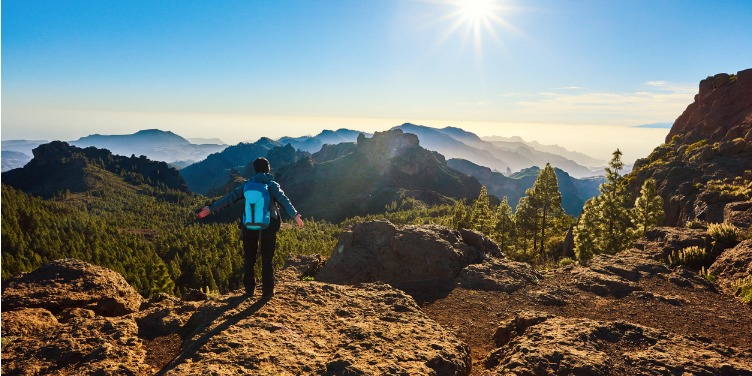 Hiker stands admiring the views of pine trees and mountains in Gran Canaria