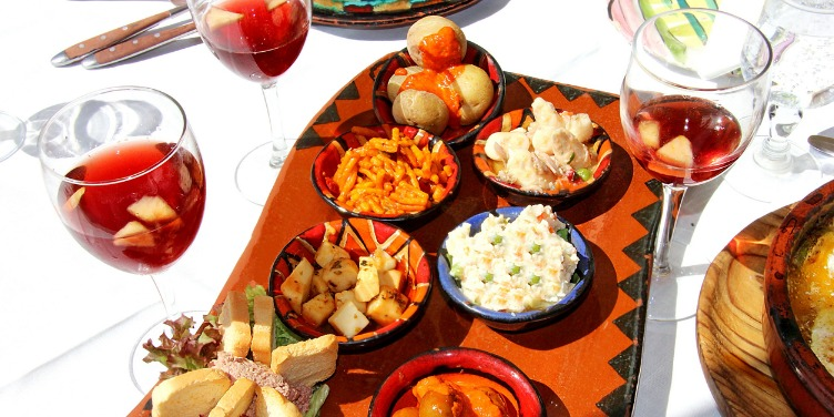 Spanish salad spread and wine on a table