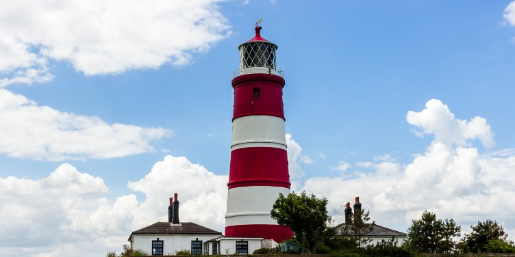 Happisburgh's red and white striped lighthouse against a blue sky
