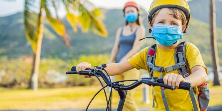 Kid riding bicycle with face mask and helmet